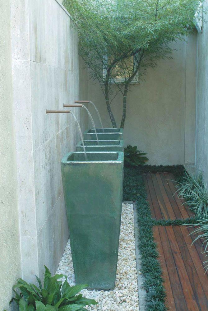 Neste projeto o trio de vasos ameniza a altura da parede e dá um ar oriental ao estreito jardim, que tem bambu mossô (Phyllostachys pubescens) ao fundo, grama-preta (Ophiopogon japonicus) contornando o deque e clorofito (Chlorophytum comosum) na parede oposta aos vasos. Estas plantas são feitas para jardins de sombra ou meia-sombra.