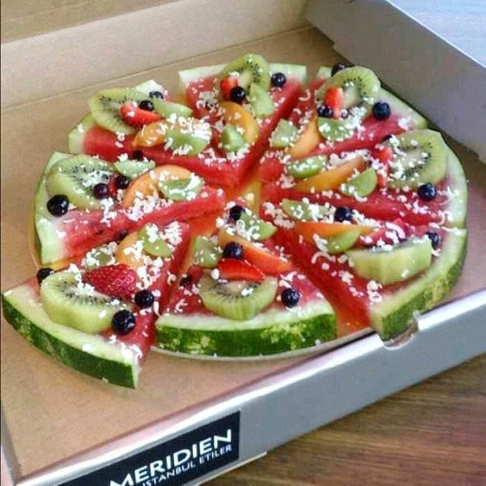 Watermelon Pizza - Step 1: Cut the thick pieces of watermelon into pizza shaped slices. Step 2: Add a layer of strawberry jam to the watermelon. Step 3: Add slices of peaches, kiwi and strawberries, then add blueberries. Step 4: Sprinkle with some shredded coconut.