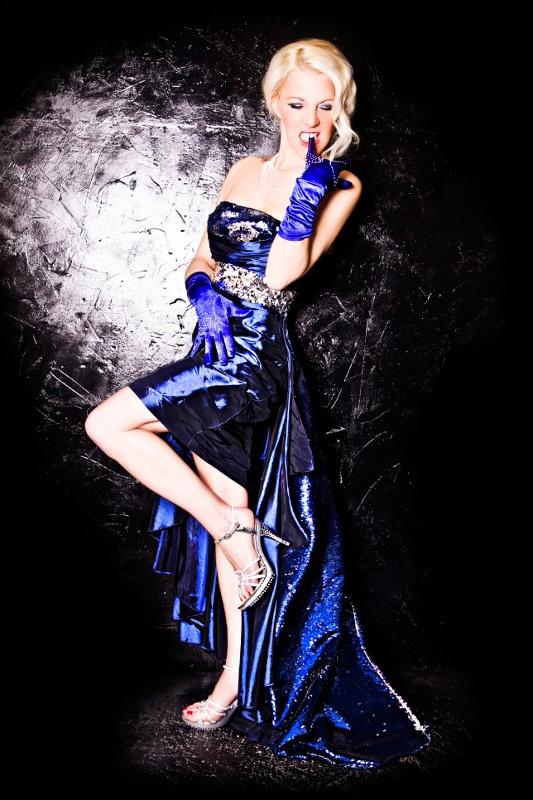 """Lizzy Malone ist eine kreative und wandelbare Tänzerin. Jedoch ist sie spezialisiert auf den Stil des klassischen Burlesque.  Ob als  Diva, Army  Girl , Witwe,  Ägypterin oder andere Charaktere, in  ihren Shows zieht sie ihre Betrachter in den Bann der """"alten"""" Zeit und des Glamours. Durch ihre klassische Ausbildung im Tanz belebt sie die Bühne mit eleganter, sinnlicher Bewegung und einem Hauch Erotik."""