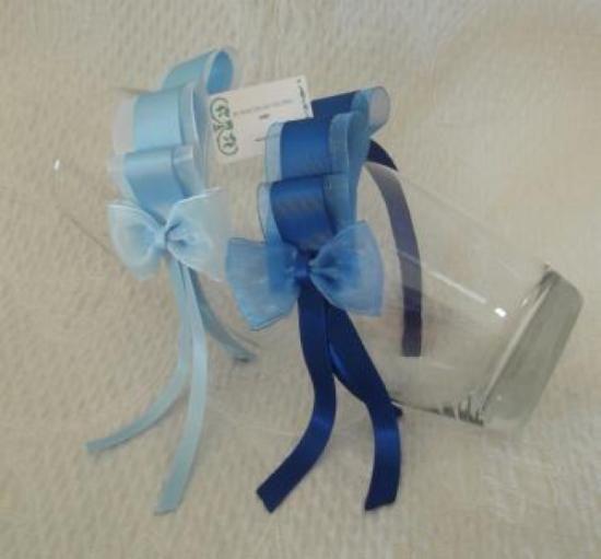 Diadema forrada de raso, adornada con lazo de organdí y falla realizando tres pliegues redondeados, rematados con una moña de organdí y raso. Gama de azul.