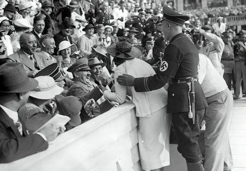 Mulher com o chapéu vermelho   Hitler reage ao beijo de mulher americana animado com os Jogos Olímpicos de Berlim de 1936  Pouco antes da chegada de 1500 metros de natação estilo livre dos homens, uma mulher em um chapéu vermelho, a quem Guardas Negros repetidamente impedido de fotografar Hitler de perto, rompeu o cordão de isolamento durante a emoção da chegada da prova, balançou Hitler pela mão e, em seguida, beijou-o, enquanto a multidão de 20.000 abalou com o riso. Hitler, que estava de…
