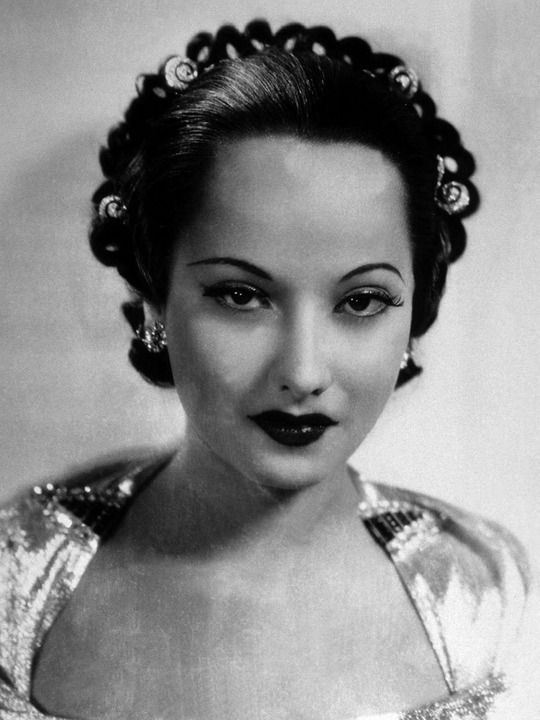 """Merle Oberon wearing two dress clips on the neckline of her dress an diamond """"curls"""" in her hair."""