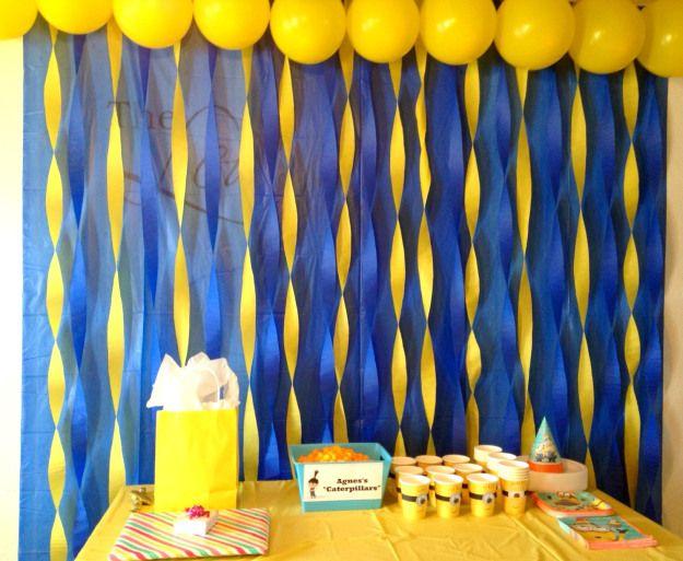 Fondo de mesa decorado de colores amarillo y azul con serpentinas para fiesta Minions. #FiestaMinions