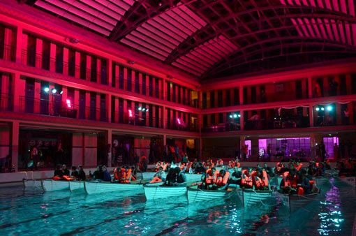 """In Paris, France an audience watches """"Life of Pi"""" in lifeboats inside a swimming pool."""