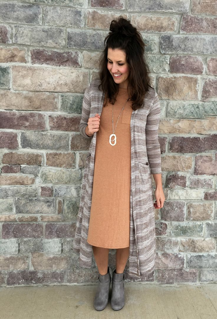 Lularoe Carly dress in tan beige camel color. (Is that legging material?!) Paired with a striped Sarah duster cardigan, gray wedge booties and a long metallic gold necklace. LOVE this outfit idea!