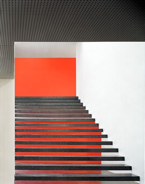 Great contrast/color scheme. The dark orange wall draws you up. Staircase inside