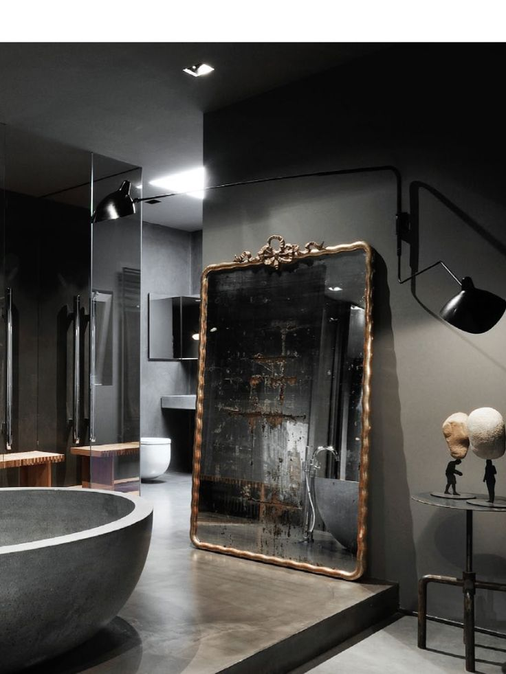 Antique gilded French mirror, matte gray walls, honed marble soaking tub, and smoked glass Shower Stall.