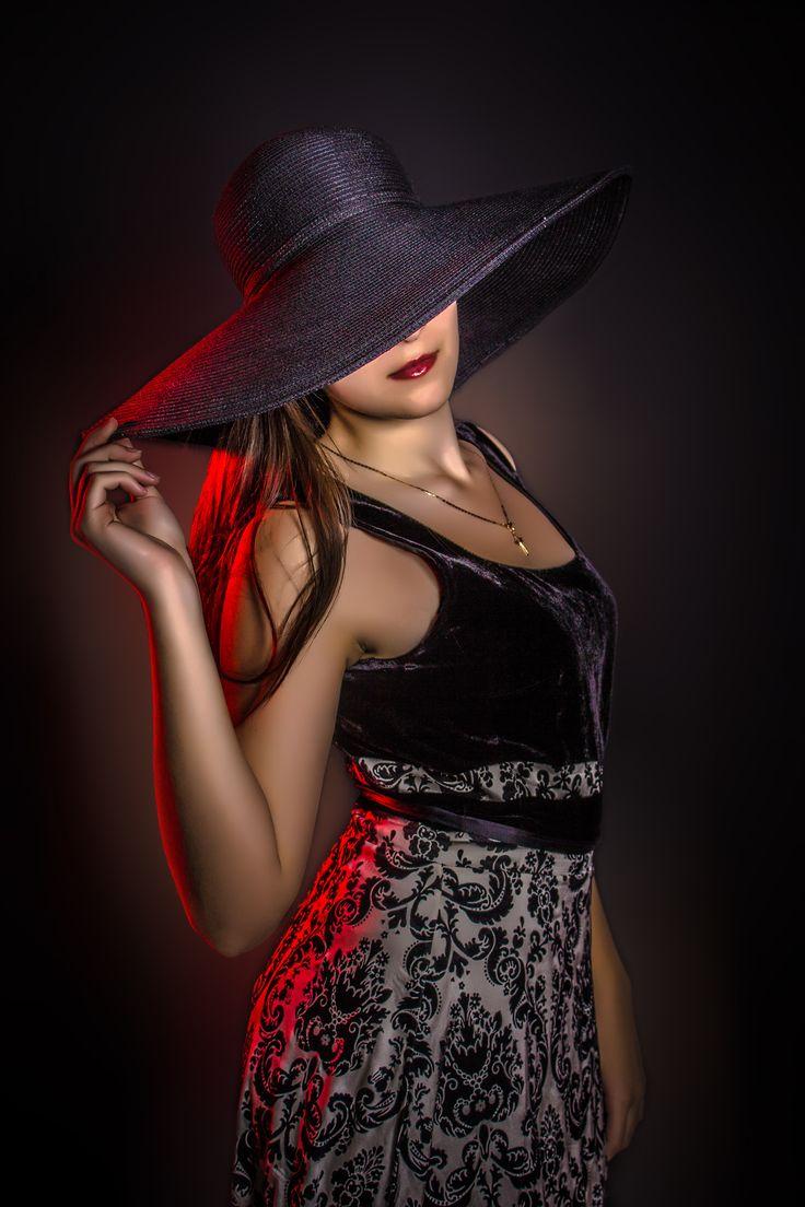 Девушка - загадка. Шляпа. Красный контровой свет. Брюнетка. Студия