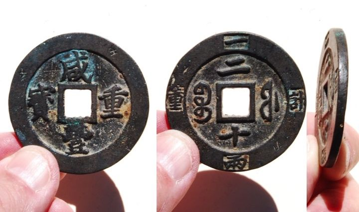 """A Xian Feng Zhong Bao (咸豐重寶) 20 cash coin, cast from 1851–1861 AD in the """"Fu"""" (福) Mint (福建寶河局), located in Fujian Province. The rim of the reverse side of the coin is stamped """"Ji Zhong Yi Liang"""" (meaning: 'weighing one tael').  Both side of this coin features some patina and encrustation.  There are also some minor dents and pitting and scratches on the rim.  Also, the character 王 is etched on front top right side rim and 刀 on the reverse lower right rim.   47mm in size; 37 grams in weight."""