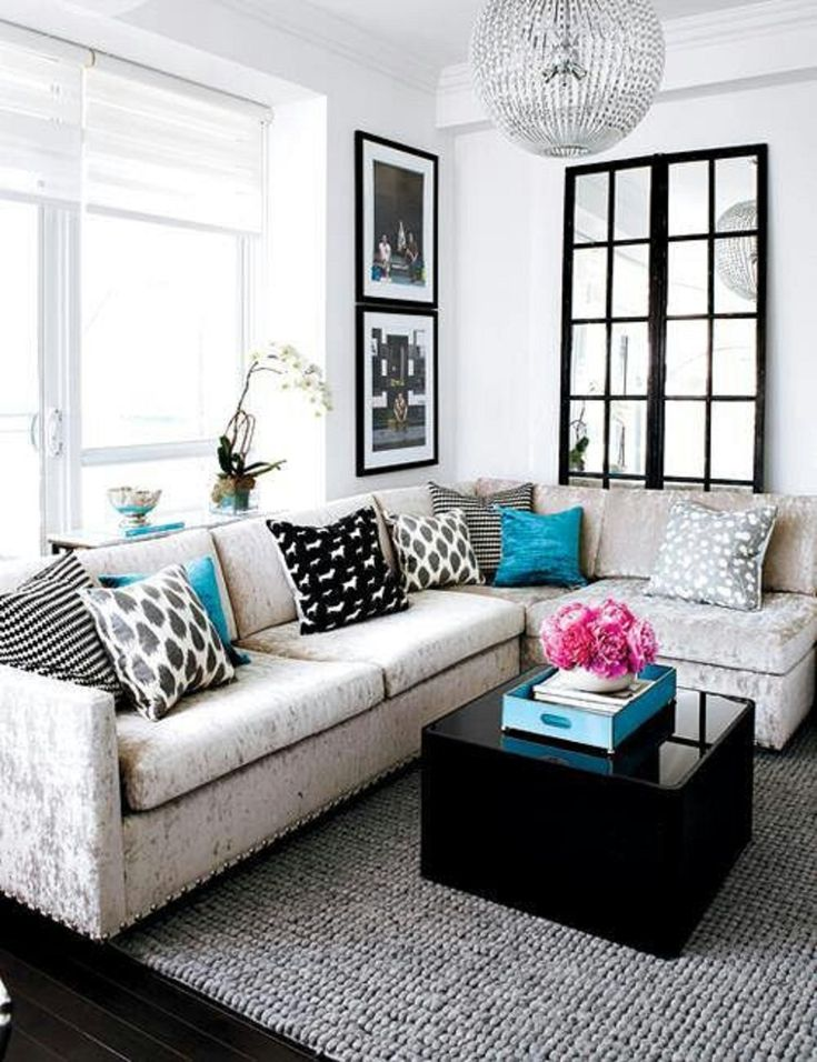 minimalist small living room interior with L-shaped sofa set and black small coffee table
