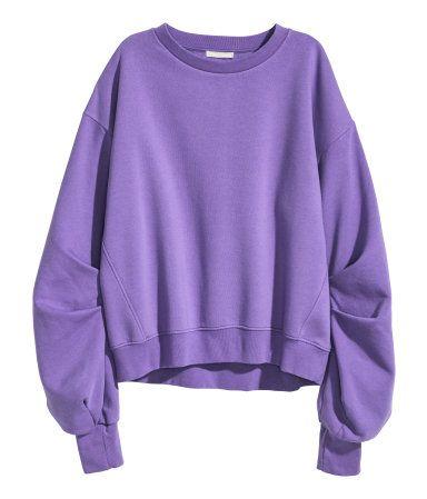 Paars. Een wijde sweater van joggingstof met een zachte, geruwde binnenkant. De sweater heeft verlaagde schoudernaden en een boord aan de onderkant en onder