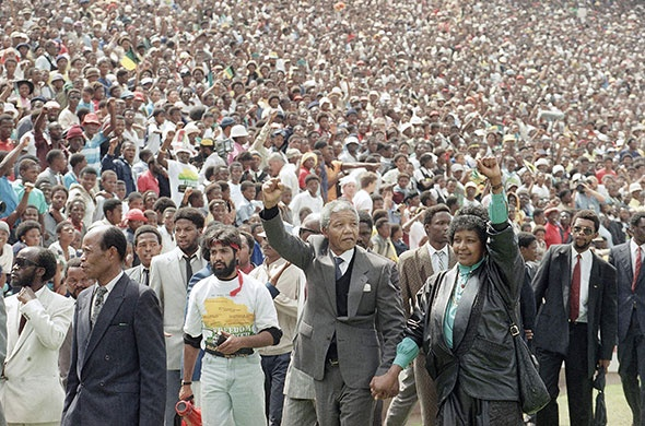 February 13, 1990: Nelson and Winnie Mandela give black power salutes as they enter Soweto's Soccer City stadium. About 120,000 African National Congress (ANC) people packed the venue to hear his speech. BelAfrique your personal travel planner - www.BelAfrique.com