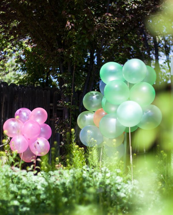 Green and pink balloon stakes in a backyard setting