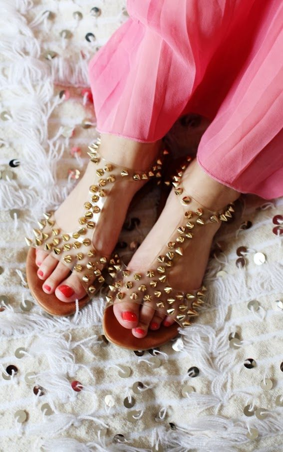 Cute sandals with golden studs on transparent