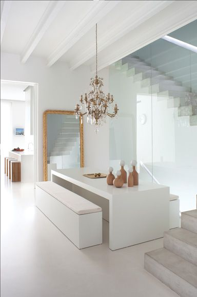 Modern lines and planes with a nice touch of vintage(the chandelier), not to mention the loads of light the white accentuates:
