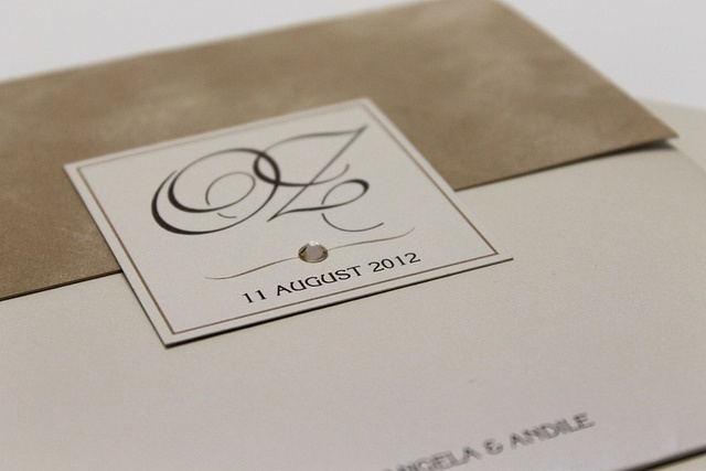 This pouch invitation includes a textural element of champagne suede. A Swarovski crystal finishes it off nicely.    www.facebook.com/RubyGreyCreative