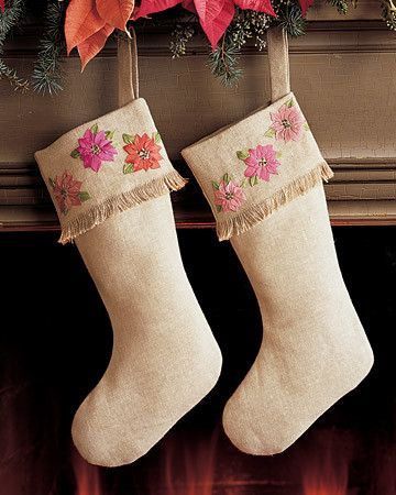 Ribbon-embroidery poinsettias decorate the fringed cuffs of a pair of Christmas stockings made from coarse bone-colored homespun linen.