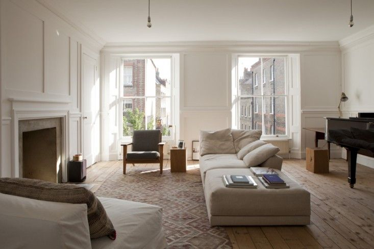 William Smalley flat in Bloomsbury, silver bottom light bulb pendants, wood floors with kilim, white paneled walls | Remodelista