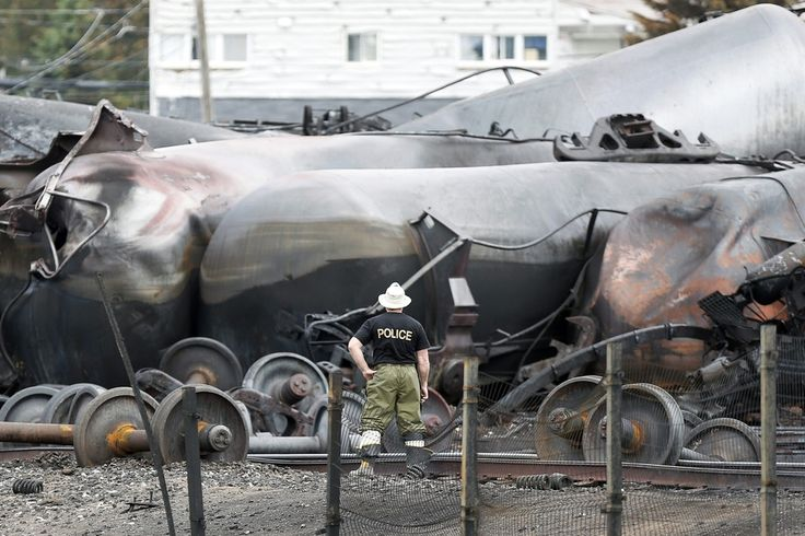 DISASTER SCENE: A police officer looked at wrecked trains in Lac-Mégantic, Quebec, Tuesday, three days after a runaway oil train smashed into the town. Thirteen people are confirmed dead and nearly 40 remain missing. (Mathieu Belanger/Reuters)