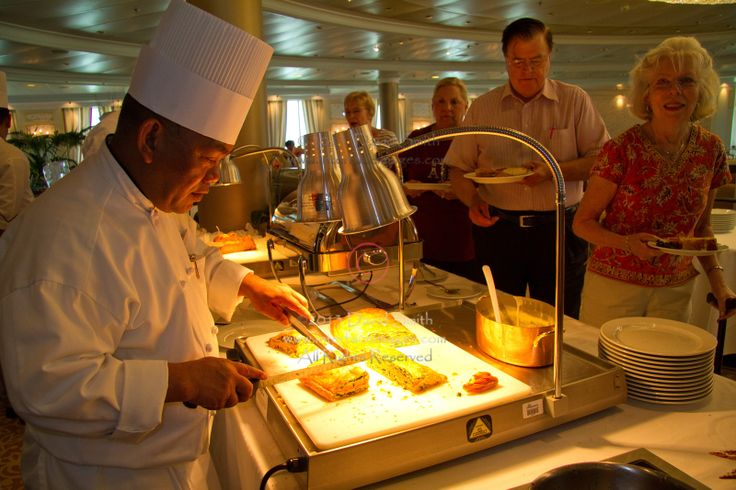 Chef carving salmon Wellington at a cruise ship buffet buffet