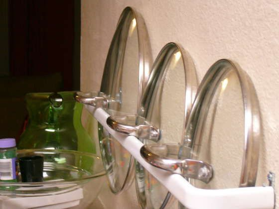 Use curtain rods on the inside of cabinet doors to hold your pot lids!!