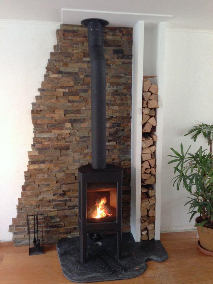 Kamin aus rustikalem Schiefer mit Stuckwänden aus Bausteinen und