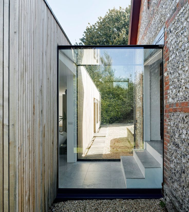 Architect Adam Knibb has added a timber-clad extension to a house in Hampshire, which is connected to the former barn building by a frameless glass box. A glass hallway
