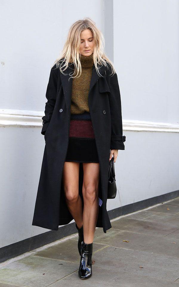 Lucy Williams posa para foto de street style vestindo maxi turtleneck de tricot, mini saia preta, casaco sobretudo preto e botas de verniz