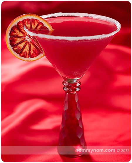 Bloody Valentine Martini    (■2 shots Absolute Mandarin Vodka  ■Juice of 3 Blood Oranges (about 1 cup)  ■Splash of Campari  ■2 Slices of Blood Orange, for garnish  ■White Sugar, to rim the glass)