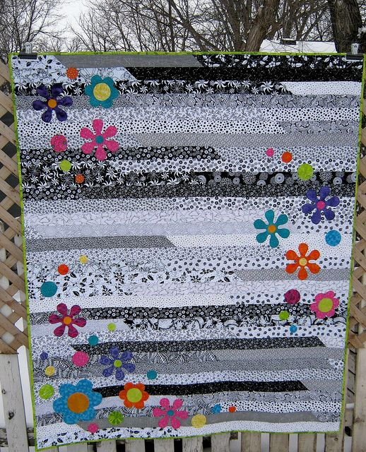 Another idea for black, white and gray. It's just a jelly roll race quilt with colorful appliquéd flowers. Would be very easy to do and make an adult sized throw. Adding this to my list!