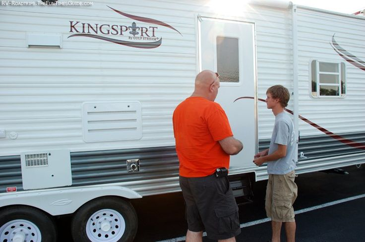 Inspecting the exterior of a used RV travel trailer.