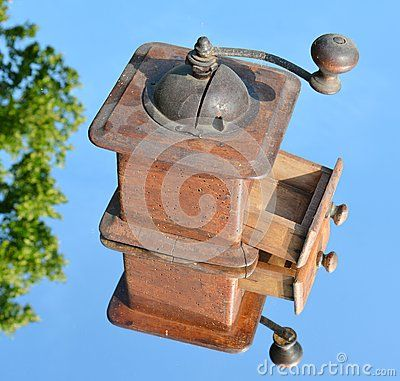 An isolated traditional coffee grinder on an abstract background.