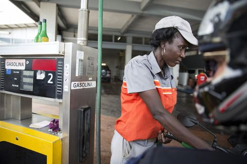 A gas station attendant fills a vehicle with gasoline at a petrol pump in Luanda, Angola. Photographer: Simon Dawson/Bloomberg