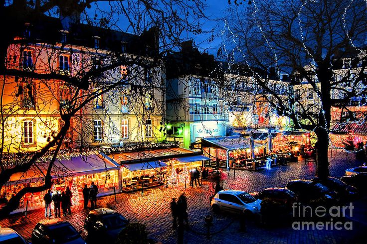 Place Chateaubriand at night in de quaint medieval French city of Saint-Malo in de Brittany region of France with colorful lights on restaurant ps n popular stores open late for tourists in de evening.