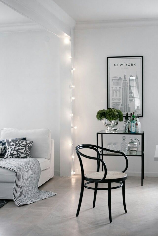 White bedroom with highlights of black furniture. White painted floors make this space peaceful and simply beautiful. Looking for: white floorboards, black furniture, black picture frame, black and white decor