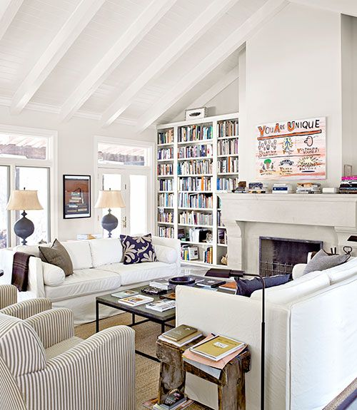 Shabby Chic sofas square off across a zinc-topped coffee table in the living room of this Texas ranch. A Jim Torok painting hangs above the mantel. The walls are painted Shaded White by Farrow