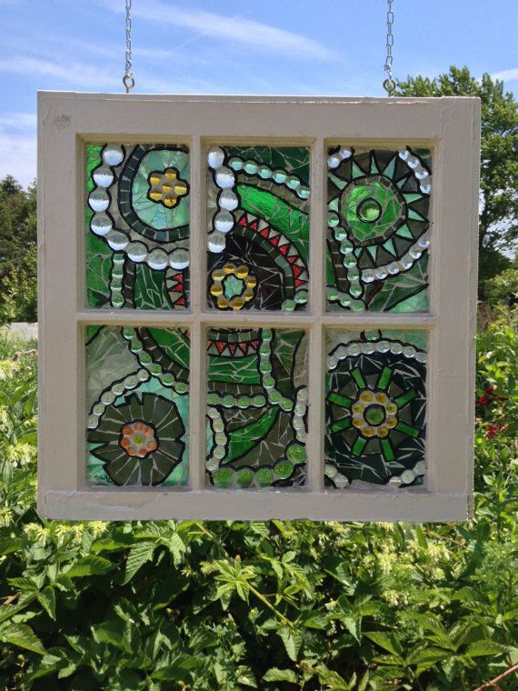 This is a handmade original design glass mosaic features multiple overlapping circles in various shades of green translucent and transparent glass with orange and yellow glass highlights. It has been created in a vintage six pane repurposed window. The image is inspired by gardening planting guilds. It is made using hand cut stained glass and glass nuggets adhered directly onto the windows existing pane. The window has been grouted, highlighted and sealed.   By using glass-on-glass…