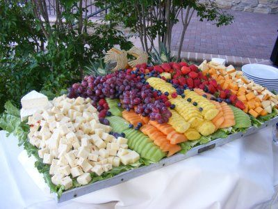 Set an appetizer table display of tropical fruits and cheese for ...