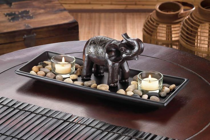 A touch of African style turns two simple candles into dramatically fantastic decor! A carved elephant statue stands guard over a collection of polished rocks and two clear glass candle cups, all set on a long tray that will look great on your table or mantel. Candles not included.