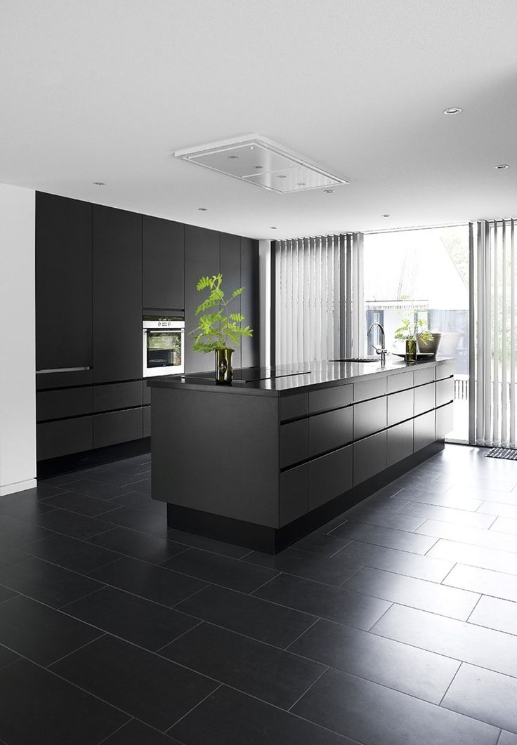 Minimalistic and stylish kitchen in dull black with smooth cabinet surfaces.