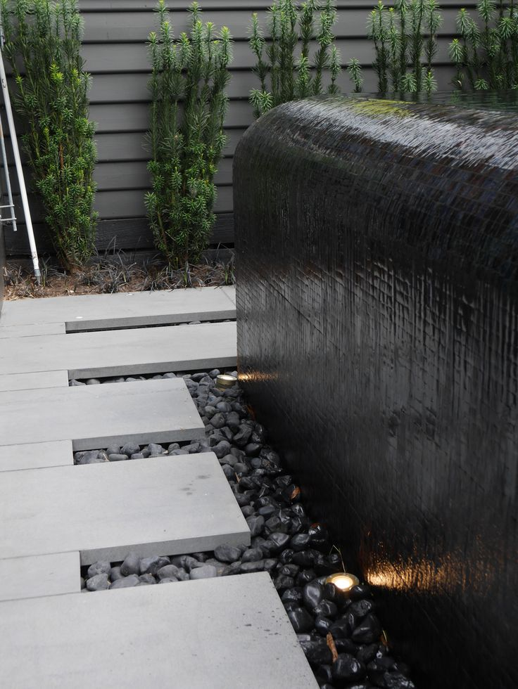 Curved infinity edge pool facing the living space. A great use of a black glass mosaic pool tile disappearing into a hidden balance tank. Pinned to Pool Design - Infinity Edges by Darin Bradbury of BASK Pool Design, Melbourne