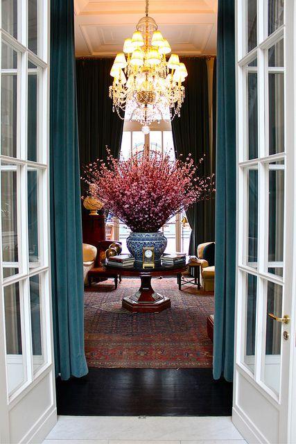 Grand entrance - Ralph Lauren interior with cherry blossoms, large chandelier, rug, velvet draperies