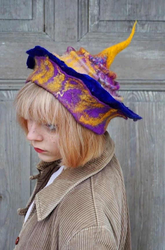 Beautiful hand felted hat with tip and double brim like crown, one of a kind, in shades of purple and yellow. You can wear it in different ways! Its made of merino wool and silk fabric decorated with wool curls and hand-shaped. Good for any time of year, it can be an excellent complement to
