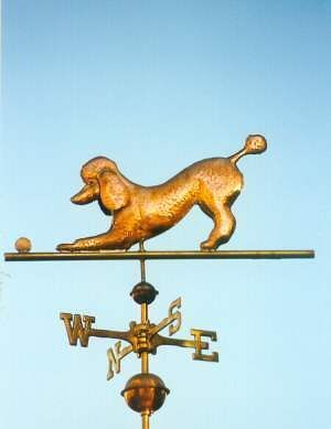 Poodle Weathervane Playing with Ball  by West Coast Weather Vanes.  This copper Poodle Dog weathervane features glass eyes, optional gold leafed patterns and distinctive tooling which gives the fur a realistic texture on the body.   Customers can provide photographs of their special canine pets for a customized  weather vane depicting  their favorite dog.
