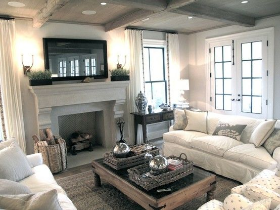 Chic, cozy living room with framed TV over stone fireplace...