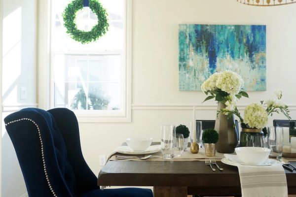 Easy and affordable dining table setting tips from Eggshell Home. Elegant green and gold tablescape. Blue velvet chair. Boxwood wreath.
