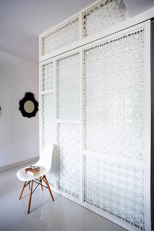 This customised white metal screen attached to glass sliding doors acts as a divider between the living room and kitchen. A combination of patterns on the metal screen liven up the space with an oriental touch.