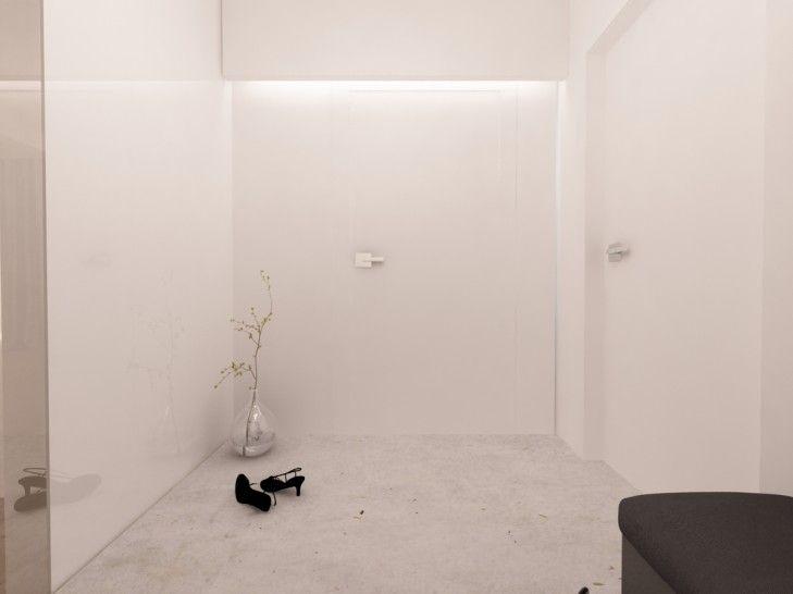 Projekt wnętrza minimalistycznego holu w bieli. Ze szczeliny w suficie podwieszanym wypływa światło podkreślając czystą formę ściany.