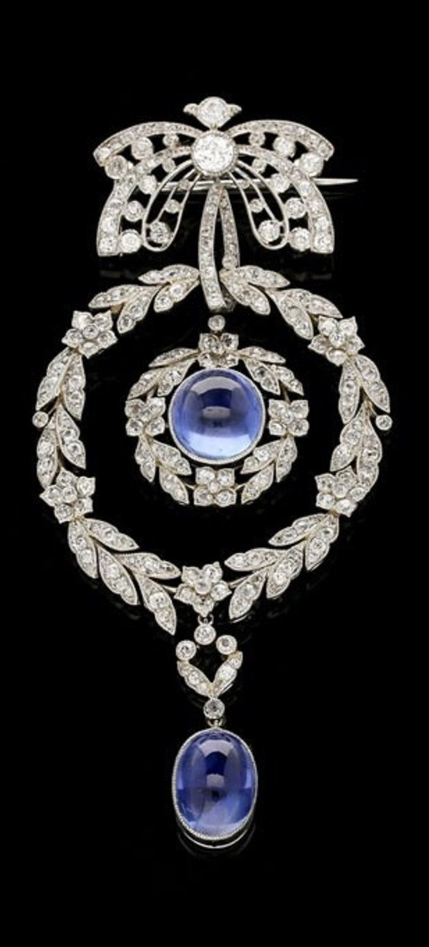 A stunning Belle Epoque sapphire and diamond brooch/pendant, circa 1905. Designed as an openwork double ribbon bow motif set with old and rose-cut diamonds, suspending an oval cabochon sapphire rub over set within a floral wreath surround, encircled by another larger wreath both diamond set throughout and with an oval cabochon sapphire articulated drop, all in platinum with fine millegrain edging. #DiamondBrooches