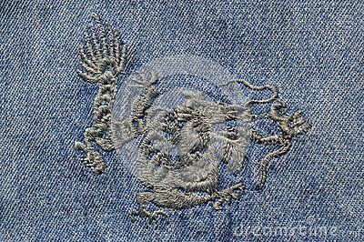 Machine embroidery in the form of a Chinese dragon on blue denim.